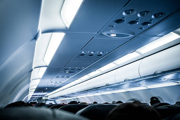 Blurred image of airplane interior in blue color filter Blurred image of airplane interior in blue color filter passenger cabin stock pictures, royalty-free photos & images