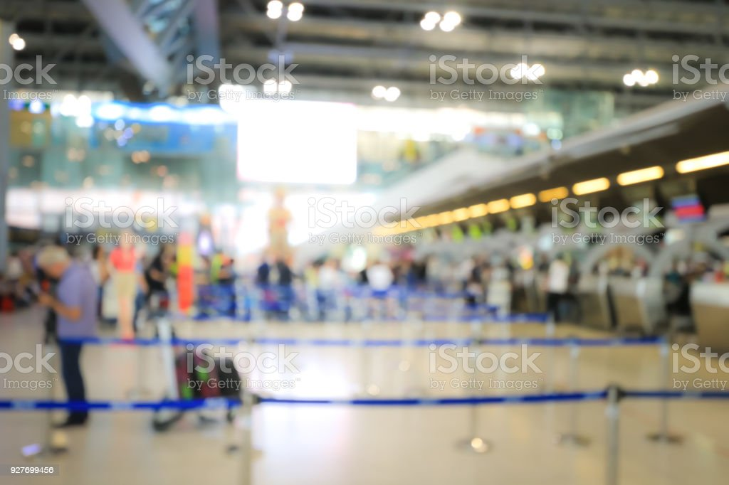 Blurred image of airport check-in counters with passengers and crowd of people control barriers with bokeh in international airport, que, travel, tourism, business concept Abstract Blur Background. stock photo