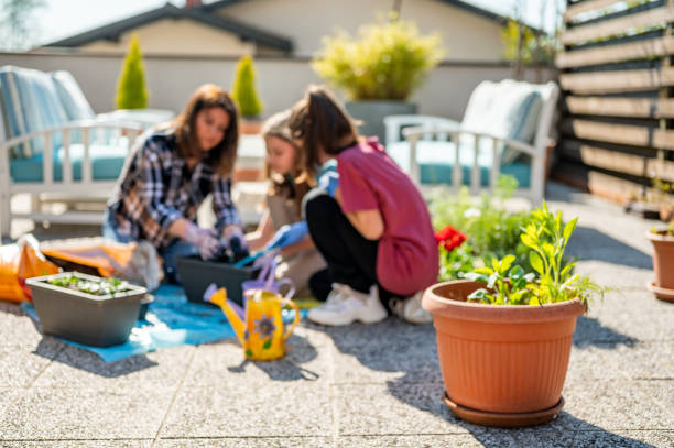 Verschwommenes Bild einer erwachsenen Frau und zwei junger Mädchen, die auf der Terrasse pflanzen – Foto