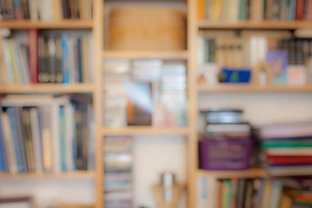 blurred image of bookshelves with books - boekenplank stockfoto's en -beelden
