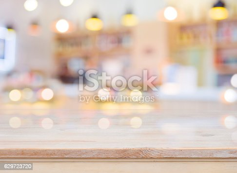 886308526 istock photo Blurred image of cafe interior with wooden table in front 629723720