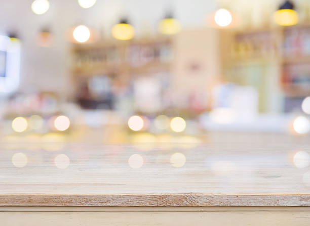 blurred image of cafe interior with wooden table in front - store counter stock photos and pictures