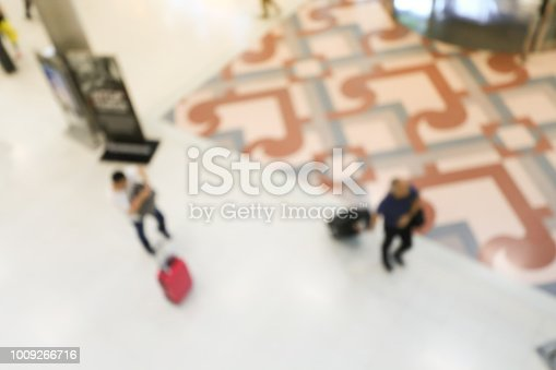 istock blurred image of crowd of travelling people or passenger walking with a luggage from flight in the international airport terminal with beautiful bokeh from the light,advertise & traveling concept. 1009266716