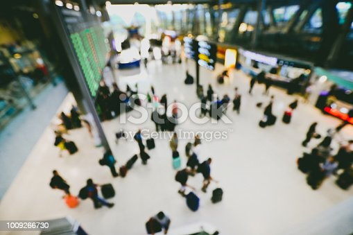 istock blurred image of crowd of travelling people or passenger walking with a luggage from flight in the international airport terminal with beautiful bokeh from the light,advertise & traveling concept. 1009266730