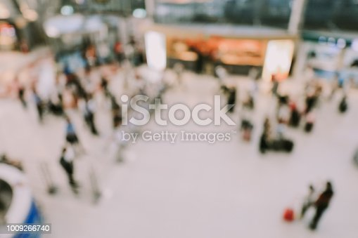 istock blurred image of crowd of travelling people or passenger walking with a luggage from flight in the international airport terminal with beautiful bokeh from the light,advertise & traveling concept. 1009266740