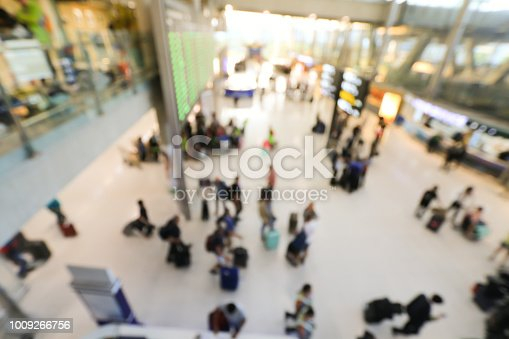 istock blurred image of crowd of travelling people or passenger walking with a luggage from flight in the international airport terminal with beautiful bokeh from the light,advertise & traveling concept. 1009266756