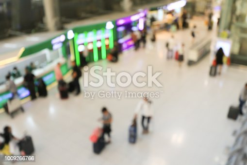 istock blurred image of crowd of travelling people or passenger walking with a luggage from flight in the international airport terminal with beautiful bokeh from the light,advertise & traveling concept. 1009266766