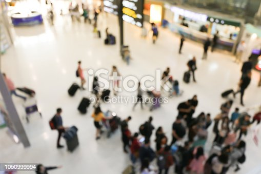 istock blurred image of crowd of travelling people or passenger walking with a luggage from flight in the international airport terminal with beautiful bokeh from the light,advertise & traveling concept. 1050999994