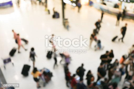 istock blurred image of crowd of travelling people or passenger walking with a luggage from flight in the international airport terminal with beautiful bokeh from the light,advertise & traveling concept. 1051000026