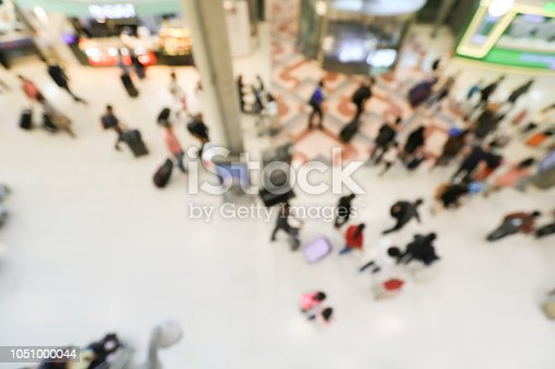 istock blurred image of crowd of travelling people or passenger walking with a luggage from flight in the international airport terminal with beautiful bokeh from the light,advertise & traveling concept. 1051000044