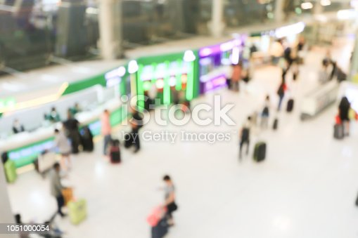 istock blurred image of crowd of travelling people or passenger walking with a luggage from flight in the international airport terminal with beautiful bokeh from the light,advertise & traveling concept. 1051000054