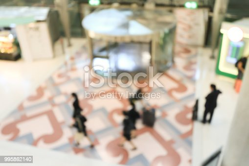 istock blurred image of crowd of travelling people or passenger walking with a luggage from flight in the international airport terminal with beautiful bokeh from the light,advertise & traveling concept. 995862140