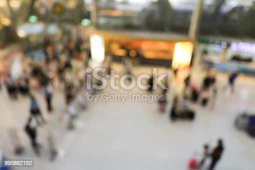 istock blurred image of crowd of travelling people or passenger walking with a luggage from flight in the international airport terminal with beautiful bokeh from the light,advertise & traveling concept. 995862152