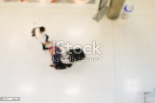 istock blurred image of crowd of travelling people or passenger walking with a luggage from flight in the international airport terminal with beautiful bokeh from the light,advertise & traveling concept. 995862254