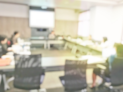 831720990 istock photo Blurred image of education people and business people sitting in conference room for profession seminar and the speaker is presenting new technology and idea sharing with the content activity project. 806298486