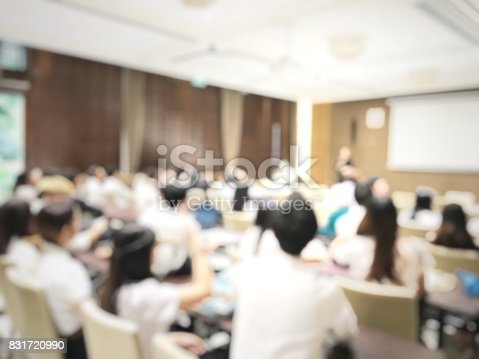 831720990istockphoto blurred image of education people and business people sitting in conference room for profession seminar and the speaker is presenting with screen projector and idea sharing with the content activity. 831720990