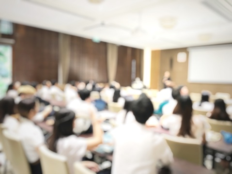 831720990 istock photo blurred image of education people and business people sitting in conference room for profession seminar and the speaker is presenting with screen projector and idea sharing with the content activity. 831720990