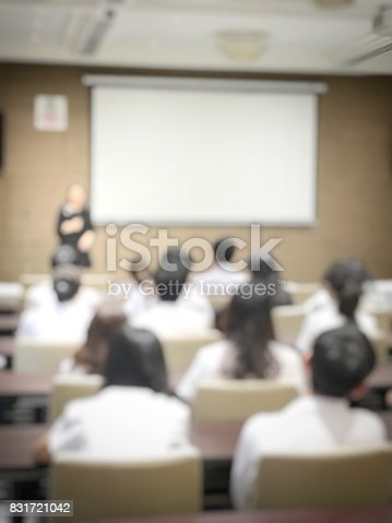 831720990istockphoto blurred image of education people and business people sitting in conference room for profession seminar and the speaker is presenting with screen projector and idea sharing with the content activity. 831721042