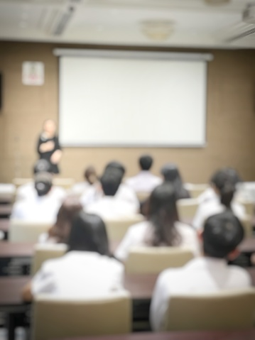 831720990 istock photo blurred image of education people and business people sitting in conference room for profession seminar and the speaker is presenting with screen projector and idea sharing with the content activity. 831721042