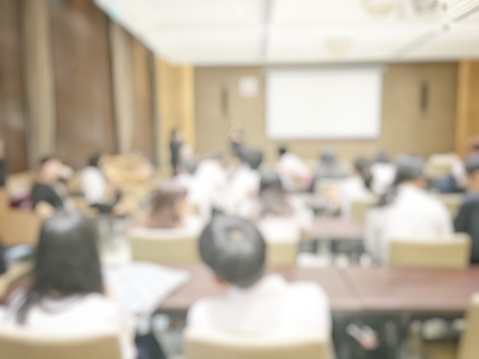 831720990 istock photo blurred image of education people and business people sitting in conference room for profession seminar and the speaker is presenting with screen projector and idea sharing with the content activity. 831721098