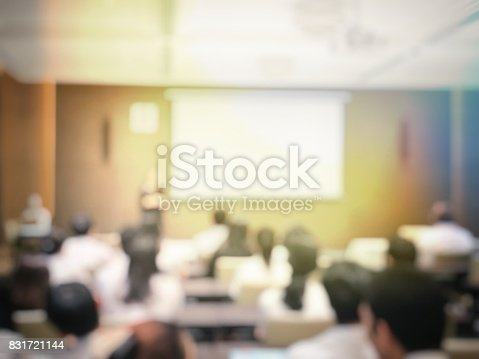 831720990istockphoto blurred image of education people and business people sitting in conference room for profession seminar and the speaker is presenting with screen projector and idea sharing with the content activity. 831721144