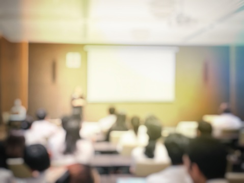 831720990 istock photo blurred image of education people and business people sitting in conference room for profession seminar and the speaker is presenting with screen projector and idea sharing with the content activity. 831721144