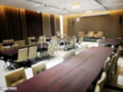 istock Blurred image of empty interior of conference room, meeting room prepare for webinar. Blurry nobody in Classroom, Office with chairs and tables. vintage tone. Abstract blur for background usage. 859076592