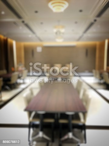 istock Blurred image of empty interior of conference room, meeting room prepare for webinar. Blurry nobody in Classroom, Office with chairs and tables. vintage tone. Abstract blur for background usage. 859076612