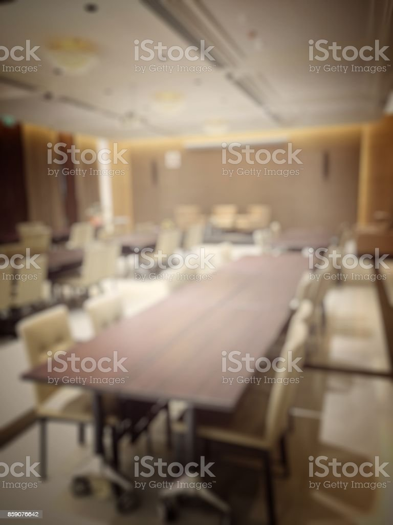 Blurred image of empty interior of conference room, meeting room prepare for webinar. Blurry nobody in Classroom, Office with chairs and tables. vintage tone. Abstract blur for background usage. stock photo