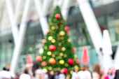 Blurred image of outdoor colorful decorated Christmas tree with people in front of shopping mall in festive season