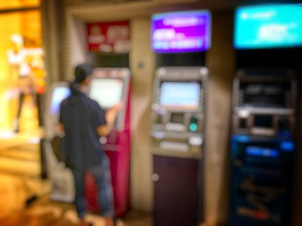 blurred image of people line up to use Banking Machine or ATM(Automatic Teller Machine) to Deposit in city at night time and can be illustration to article of people use atm stock photo