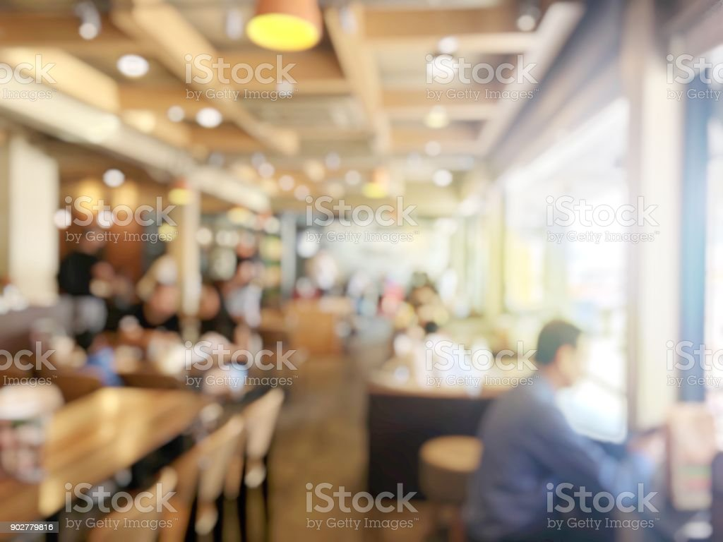 blurred image of People waiting and queuing  for order some food and make payment in Fastfood Store. vintage tone and light effect. stock photo