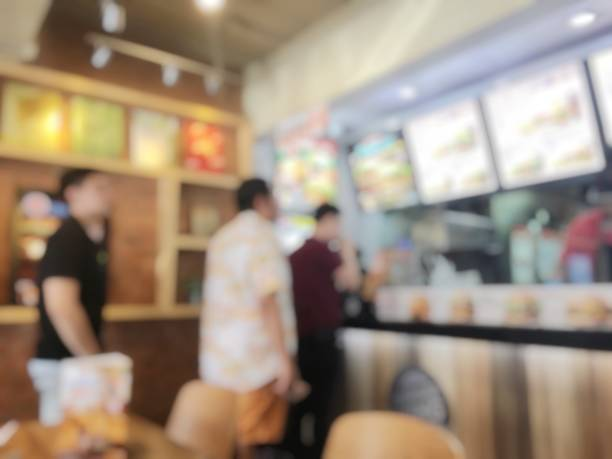 blurred image of people waiting and queuing  for order some food and make payment in fastfood store. vintage tone and light effect. - fast food restaurant stock pictures, royalty-free photos & images