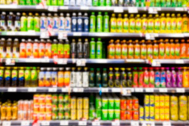 unscharfes bild des regals von getränkeflaschen im supermarkt - alkoholfreies getränk stock-fotos und bilder