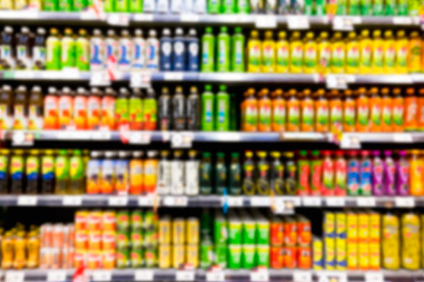 blurred image of shelf of drink bottles at supermarket - bottle soft drink foto e immagini stock