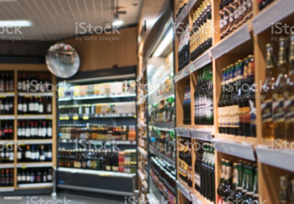 Wazig beeld van planken met alcoholische dranken in de supermarkt. foto