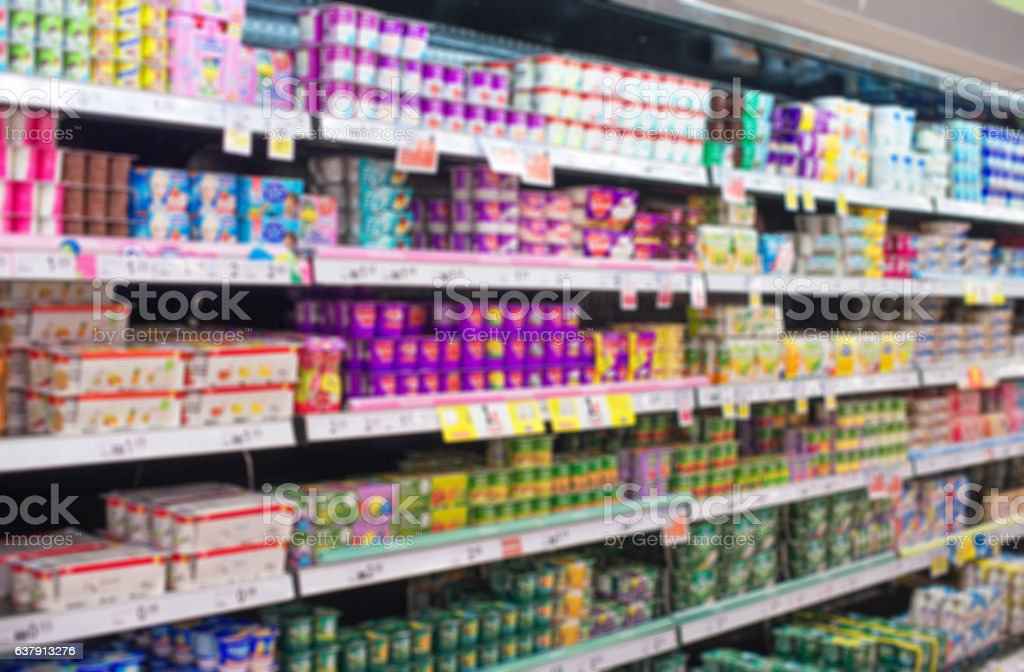 Blurred image of shelves with milk products in supermarket. stock photo