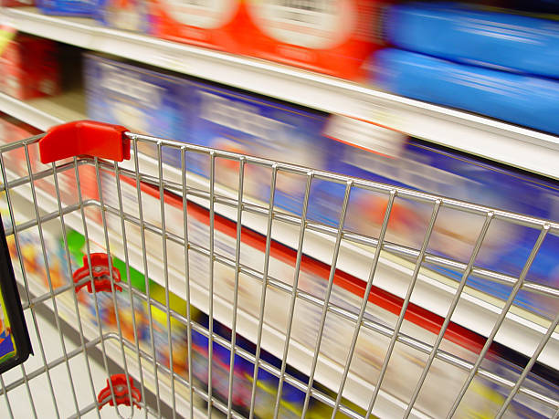 Blurred image of supermarket shopping car passing shelves stock photo