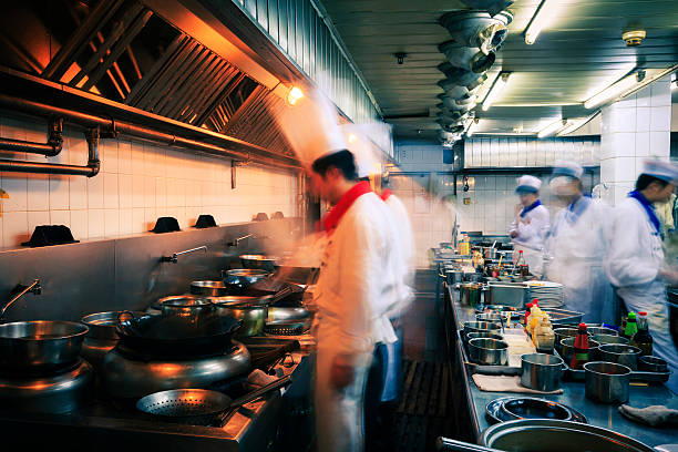blurred image of the fast pace of a restaurant kitchen - busy restaurant kitchen stock pictures, royalty-free photos & images
