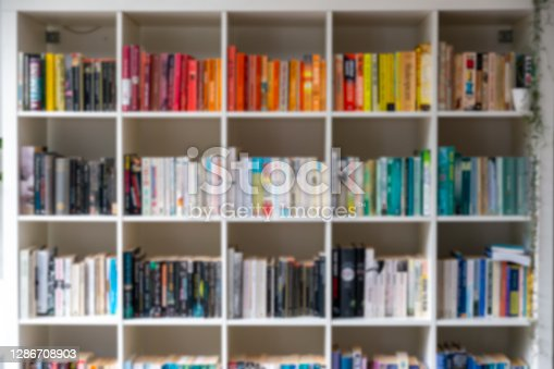 istock Blurred image of white wooden bookcase filled with books 1286708903
