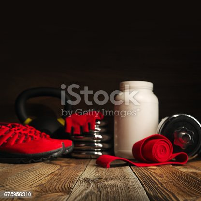 istock Blurred image Sport fitness bodybuilding healthy lifestyle and weightlifting concept gym backround Dumbbell plates White jar with whey protein Red hand wrap and red gloves on wooden floor 675956310