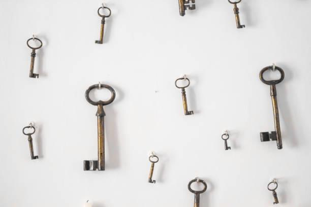 unscharfes bild-vintage-stil. hang auf die weiße wand hintergrund / antike schlüssel schlüssel tapete. - schlüssel dekorationen stock-fotos und bilder