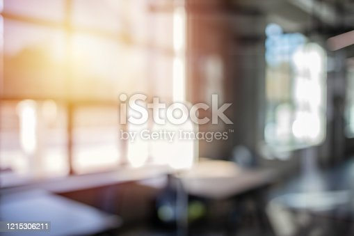 Abstract blurred in front of entrance modern glass decorative of company hall background with morning light effect for design. Blurred interior of modern office workplace a workspace design