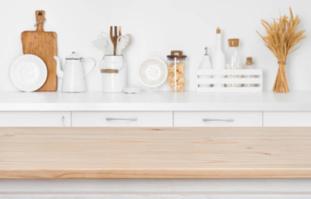 Blurred kitchen counter with utensils and ingredients over wooden table stock photo