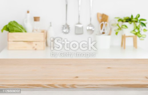 923629650istockphoto Blurred kitchen workplace with empty wooden table top in front 1129309202