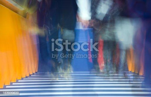 171150458istockphoto Blurred Legs of Walking People on Orange Stairs 153999600