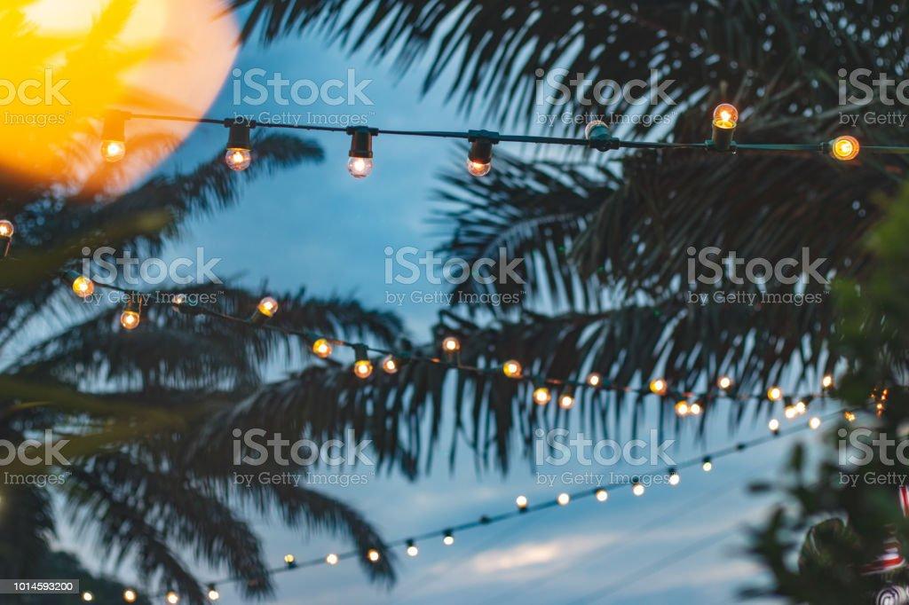 wazig licht bokeh met coconut palm tree achtergrond op zonsondergang, gele string lichten met bokeh decor in openlucht restaurant foto