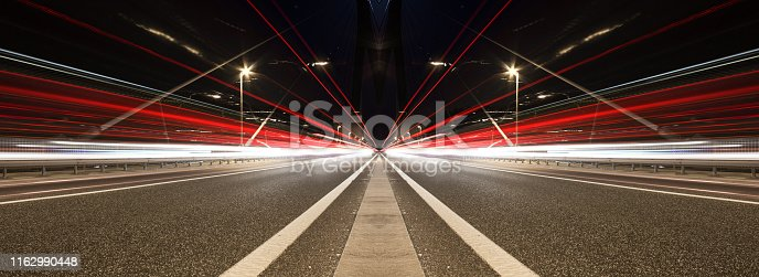 Blurred lights of vehicles. Night traffic. Bridge road at night.