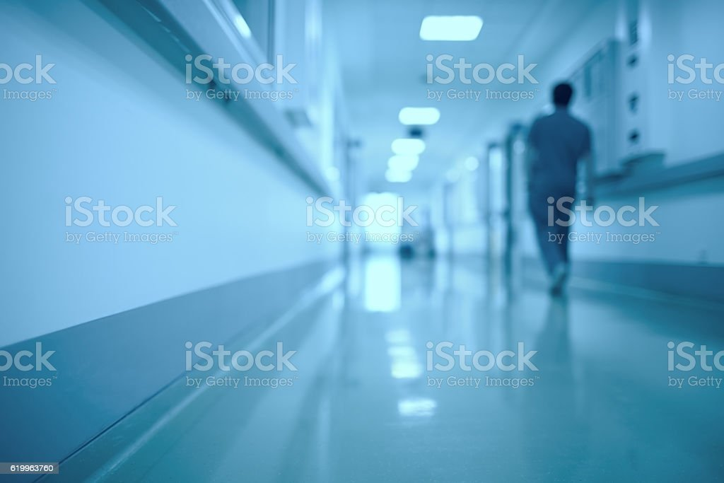 Blurred medical background. Moving human figure in the hospital corridor. stock photo