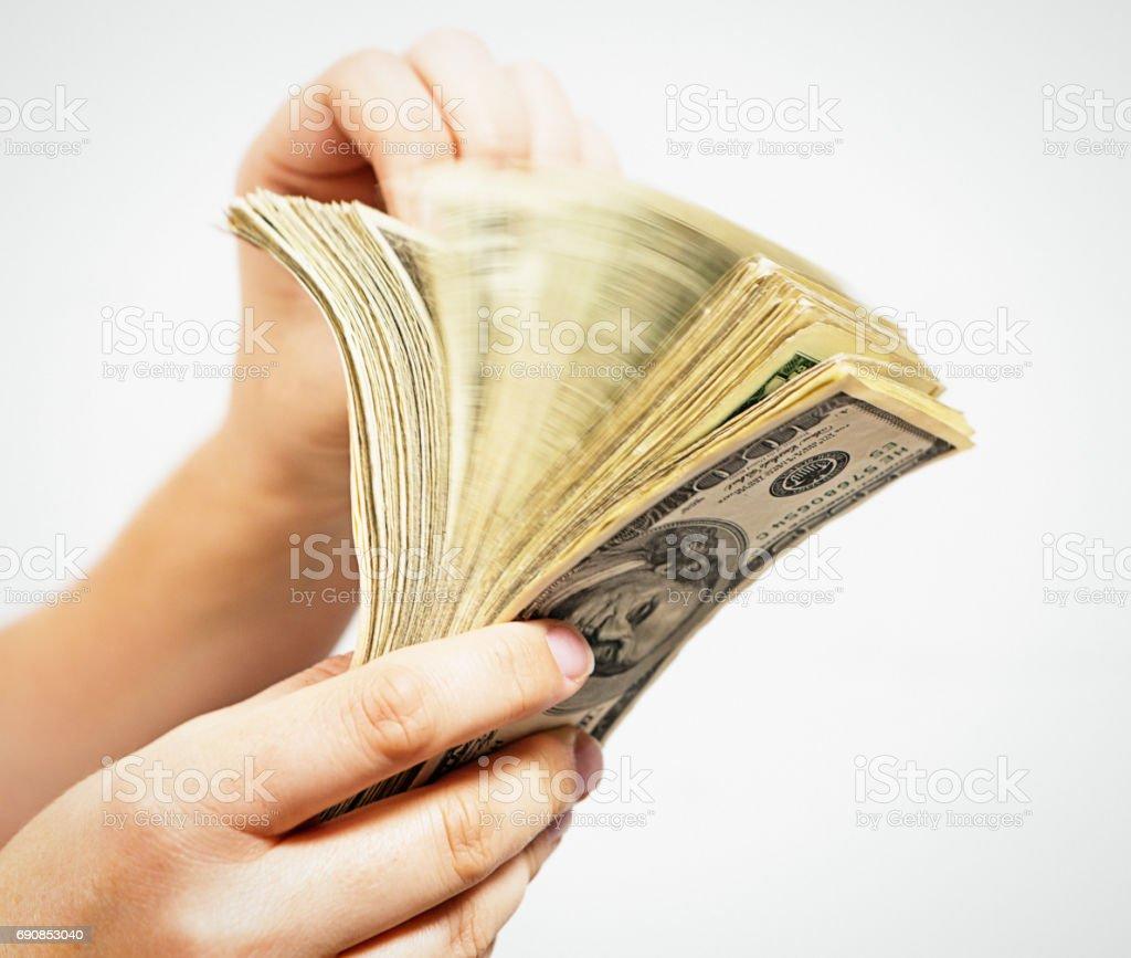 Blurred motion as hand riffles through bundle of US dollars stock photo